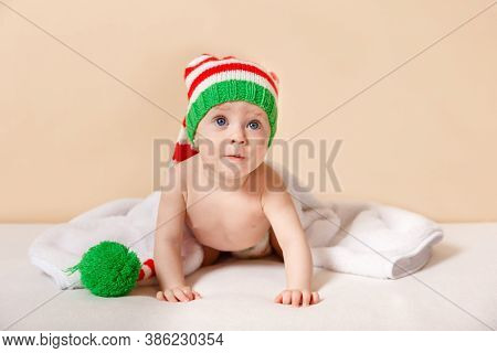 Cute Little Boy Sitting And Waiting For Santa Claus. Smiling Baby Crawling On White Blanket With San