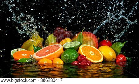Freeze Motion Shot of Fresh Fruits with Splashing Water Isolated on Black Background.