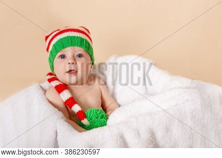 Smiling Baby Lying On White Blanket With Santa Hat And Suit. Pretty Child In Christmas Costume. Cute