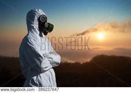 Side View Of Male Environmentalist With Crossed Arms Looking Aside While Thermal Chimneys Producing