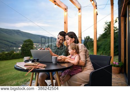 Family With Small Daughter Using Laptop Outdoors, Weekend Away In Container House In Countryside.