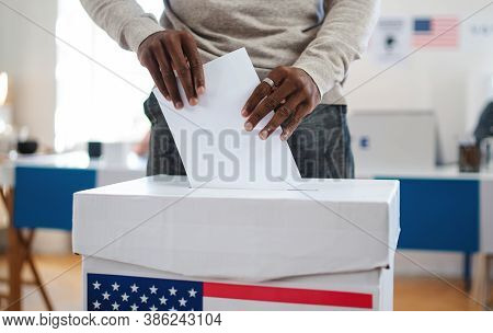 Unrecognizable African-american Man Putting His Vote In The Ballot Box, Usa Elections And Coronaviru