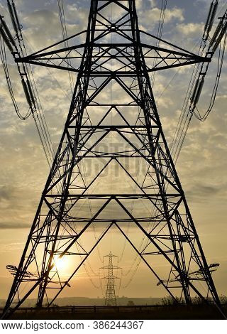 British Energy Supplier National Grid Electricity Pylon Silhouette At Sunrise Framing Distant Pylons