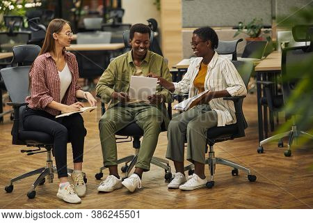 Full Length Portrait Of Three Contemporary Business People Discussing Work Project While Sitting On