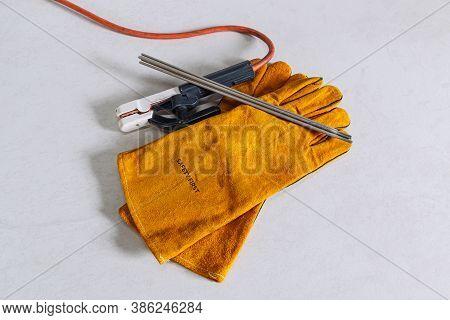 Welding Equipment Including Leather Welding Gloves,  Hand Held Welding Electrode On  Floor