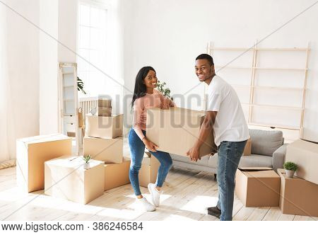 Positive Black Guy With His Girlfriend Holding Cardboard Box In Their New House On Moving Day. Mille