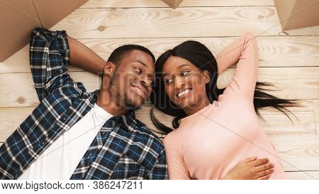 Black Millennial Woman With Her Boyfriend Lying Among Carton Boxes On Floor Of Their New House, Top