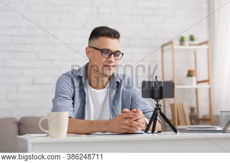 Modern Blogger Or Teacher Works From Home. Young Man Looking At Webcam, Recording Blog Or Webinar, U