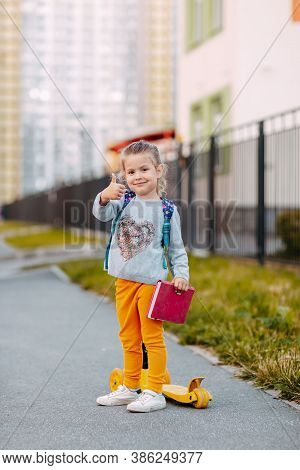 Little Girl Goes To School For The First Time. Little Student With Purple Backpack And Pink Notebook
