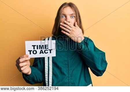 Handsome caucasian man with long hair holding time to act banner covering mouth with hand, shocked and afraid for mistake. surprised expression