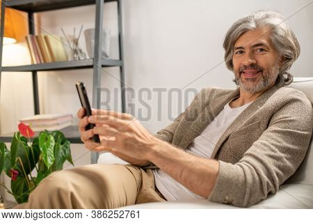 Happy mature bearded man in casualwear looking at you with smile while sitting in comfortable armchair in front of camera and using smartphone