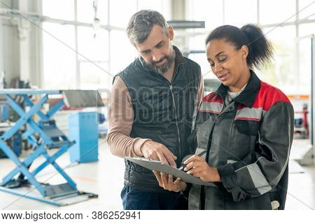 Young female worker of car maintenance service pointing at document while explaining male client some points of repair agreement