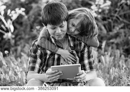 Teen boy with his younger sister sitting in a Park and using the tablet. Black and white photography.