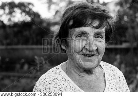 Close-up portrait of an old woman, outdoors. Black and white photography.