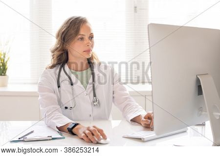 Young serious clinician in whitecoat looking through data of her patients while sitting in front of computer monitor by workplace in hospital
