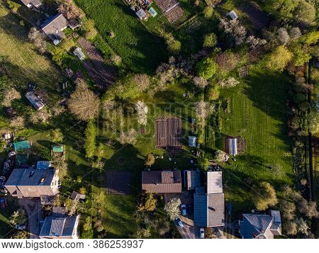 Areal Suburbs View With House Roofs, Gardens In A Evening Sun Light. Photo Taken In Latvia