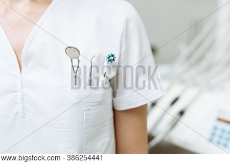 Female Dentist With Tools. A Young Doctor Stands In A Dental Office. Concept Of Attending Dentist, D