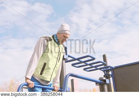 Middle Aged Man Doing Push Ups On Parallel Bars In Openair Gym. Autumn Active Lifestyle. Outdoors Sp