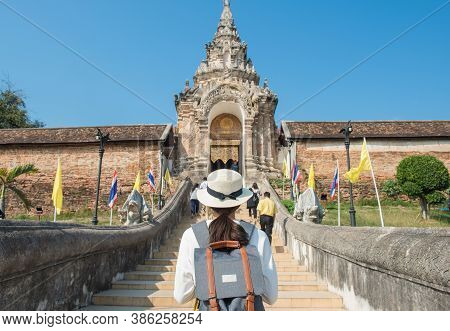 Back View Of Tourist Woman Standing In Front Of The Entrance Gate To Wat Phra That Lampang Luang An