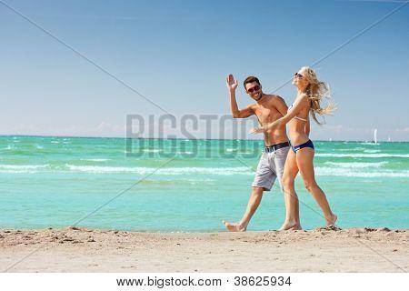 Foto de la feliz pareja caminando por la playa.