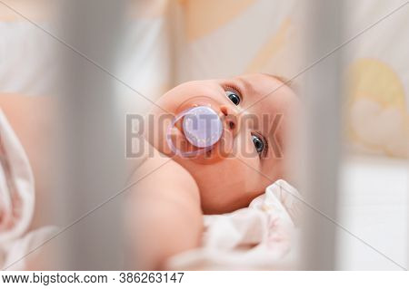 Close Up Portrait Of A Baby With A Pacifier In His Mouth, Who Is Lying In A Cradle. View Through The