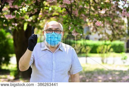 Great Idea. Man At Sakura In Protective Mask. Smell Blooming Flowers On Coronavirus Quarantine. Obse