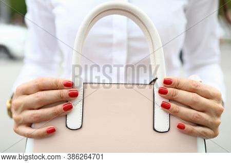 Close-up Of Woman With Beautiful Bright Red Manicure Holding Trendy Bag. Pastel Pink Colour. Stylish