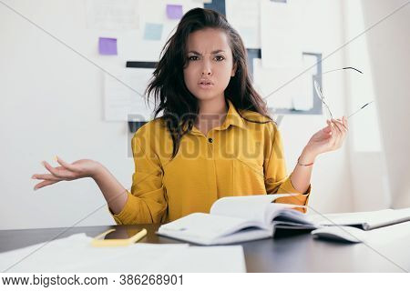 Perturbed Office Worker. Stressed Young Woman Throw Up Her Hands. Lady In Yellow Blouse Holding Glas