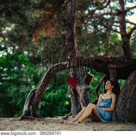 Young Woman Sits In Forest And Reads Flying And Levitating In The Air Books.
