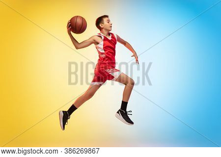 Jump High. Full Length Portrait Of Young Basketball Player In Uniform On Gradient Studio Background.