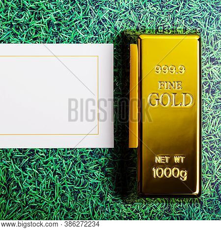 An Ingot Of Gold Metal Ingot Glittering On The Grass Background And A Card For The Inscription.