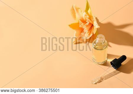 Cosmetics Oil Or Essence In Glass Bottle With Fresh Lily Flowers On Beige Background. View From Abov