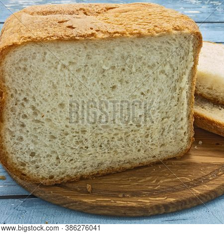 Sliced Loaf Of White Bread On A Wooden Cutting Board. Nearby Are Two Slices. Crispy Golden Crust And
