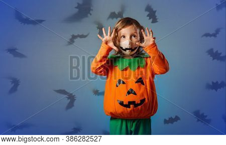 A Child In A Carnival Costume Makes A Face At The Halloween Party