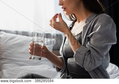 Partial View Of Brunette Woman Holding Pill And Glass Of Water At Home