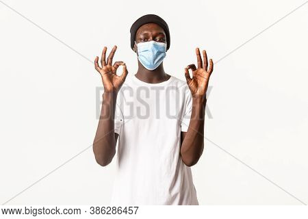 Portrait Of Satisfied African-american Handsome Guy In Medical Mask And Beanie, Staying Protected Du