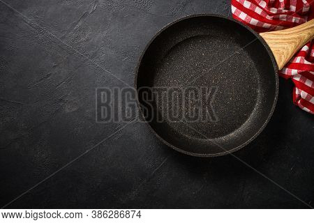 Frying Pan Or Skillet With Stone Nonstick Coating On Black Stone Table. Top View With Copy Space.