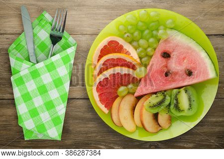 Sliced Fruit On A Borwn Wooden Background. Sliced Fruit On A Light Green Plate Fork And Knife Top Vi