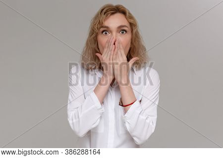 Emotion Concept. Woman Is Surprises And Touches Face With Hands Isolated On Gray Background