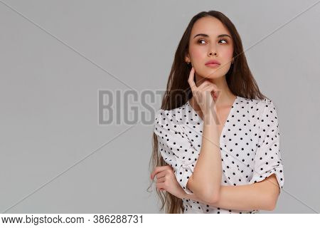Portrait Of Beautiful Young Caucasian Woman Having Doubtful Expression, Looking At Camera In Indecis