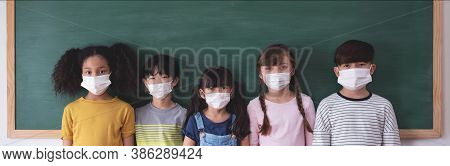 Group Of Diversity Elementary School Pupils With Protective Face Mask On Blackboard At School. Portr
