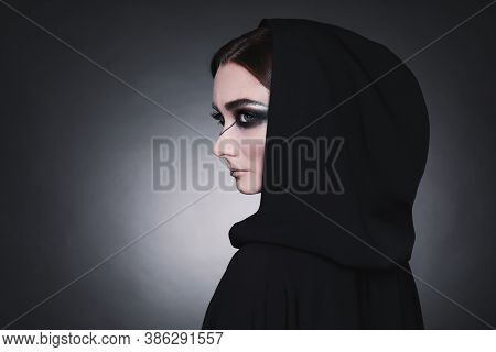 Mysterious Witch In Mantle With Hood On Dark Background. Space For Text