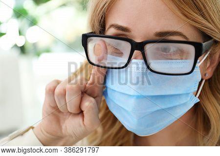 Woman Wiping Foggy Glasses Caused By Wearing Medical Mask Indoors, Closeup