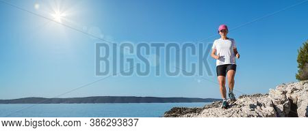 Middle-aged Female Dressed Running Sporty Clothes And Pink Cap Enjoying Morning Jogging Along The Ro