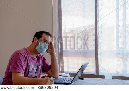 Worried Bearded Man Dressed In A Purple T-shirt Looking At The Laptop. Worry Concept