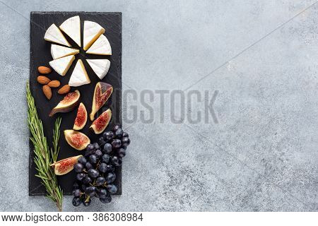 Camembert Cheese With Figs And Grapes On Slate. Top View, Copy Space. Gourmet French Cheese Platter