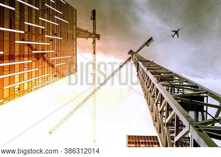 Tower Crane. Bottom View Of A Tall Construction Cranes Next To A Modern Building. Engineering And Ar