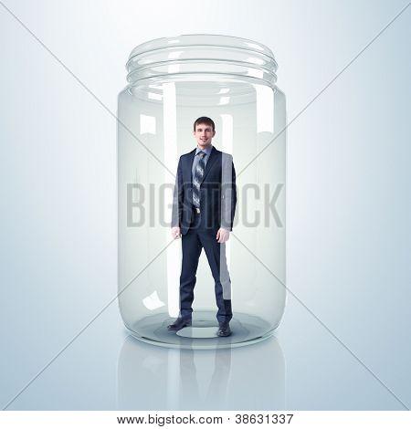 Businessman trapped inside a transparent glass jar