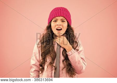 Sore Throat. Cold Climate Weather. Little Girl Sick Ill Pink Background. Kid Puffer Jacket And Knitt