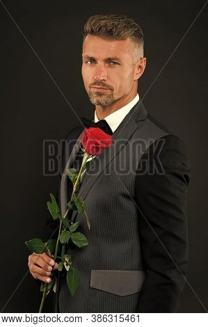 Sexy Man In Black Suit Hold Red Rose. Magician In Tuxedo With Red Rose. Celebrating 14 February. Tux